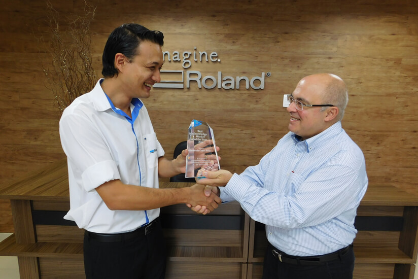 Roland DG Brasil President Celso Roberto Bento (right) presenting a trophy to Marcelo  Gomes Botao (left)