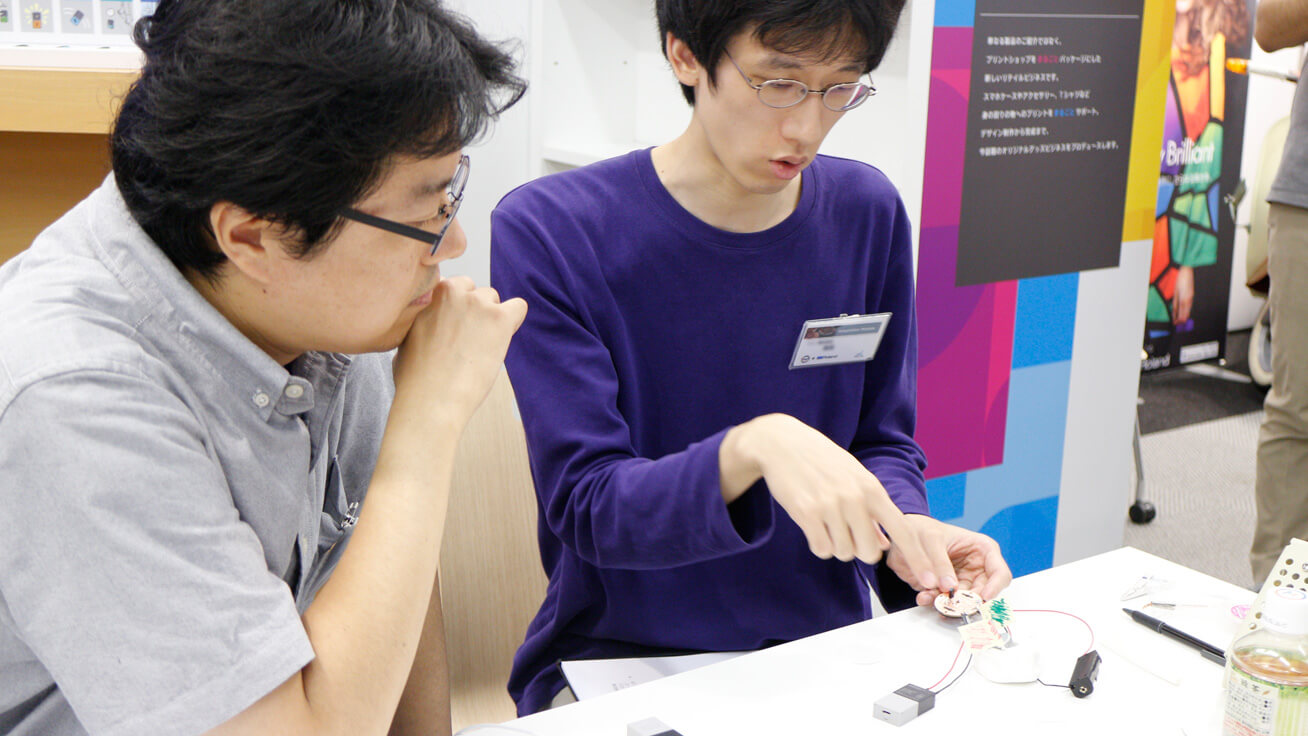 Team members discuss how to arrange circuit boards to create an interesting design.
