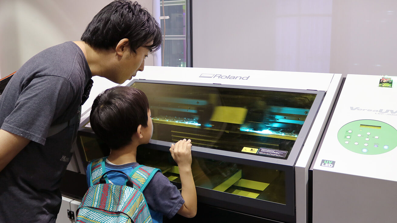 Visitors watching the UV printer in action.