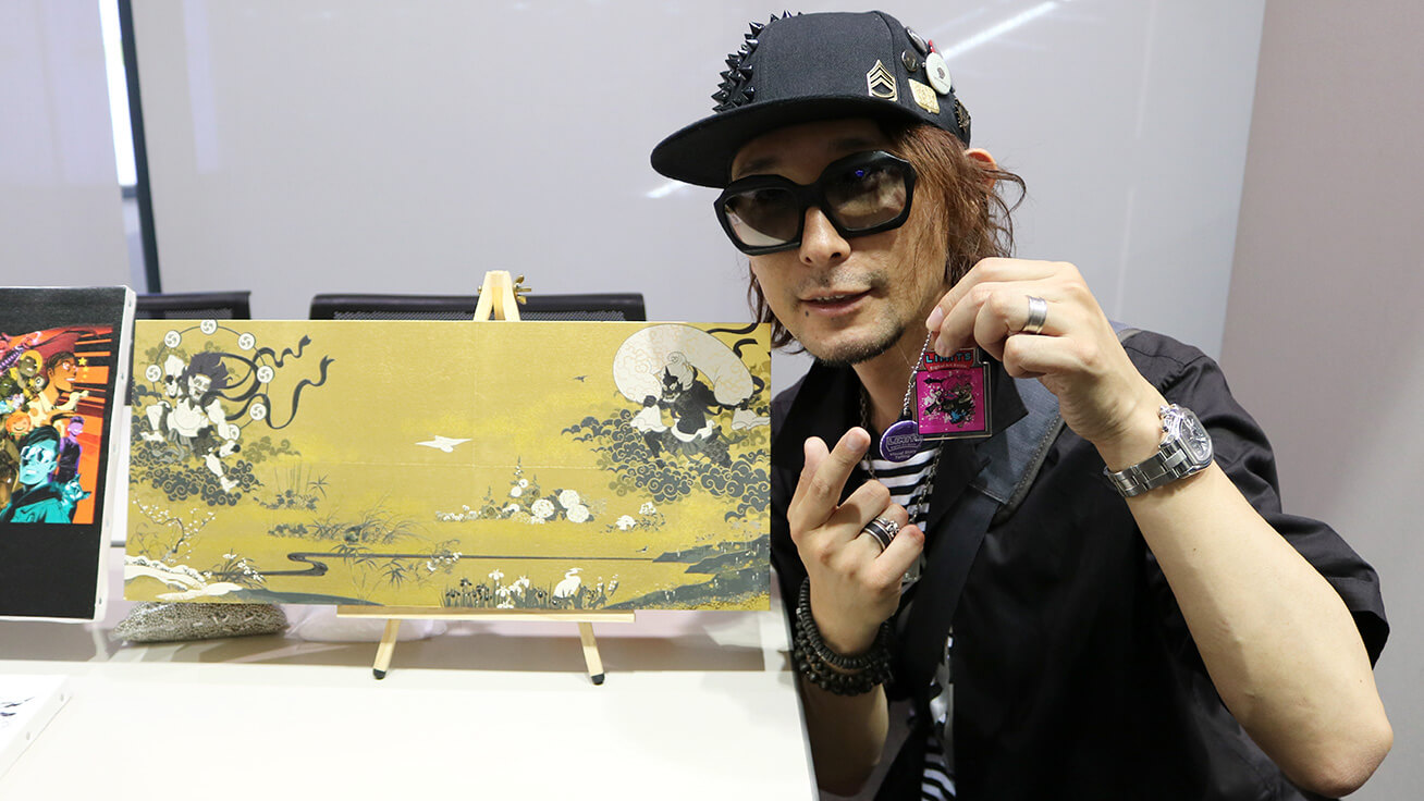 Baron Ueda (Japan) holding a one-of-a-kind creation he designed and standing in front of artwork he produced using a Roland DG UV printer.