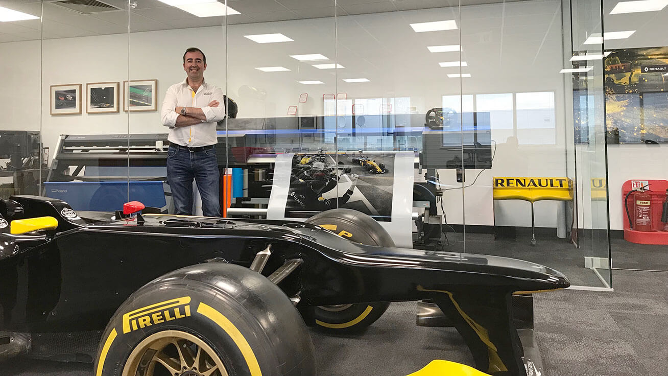 Joe McNamara, Head of Paint and Graphics at Renault Sport Formula One Team, poses with their Roland DG printer/cutter and vinyl cutter.