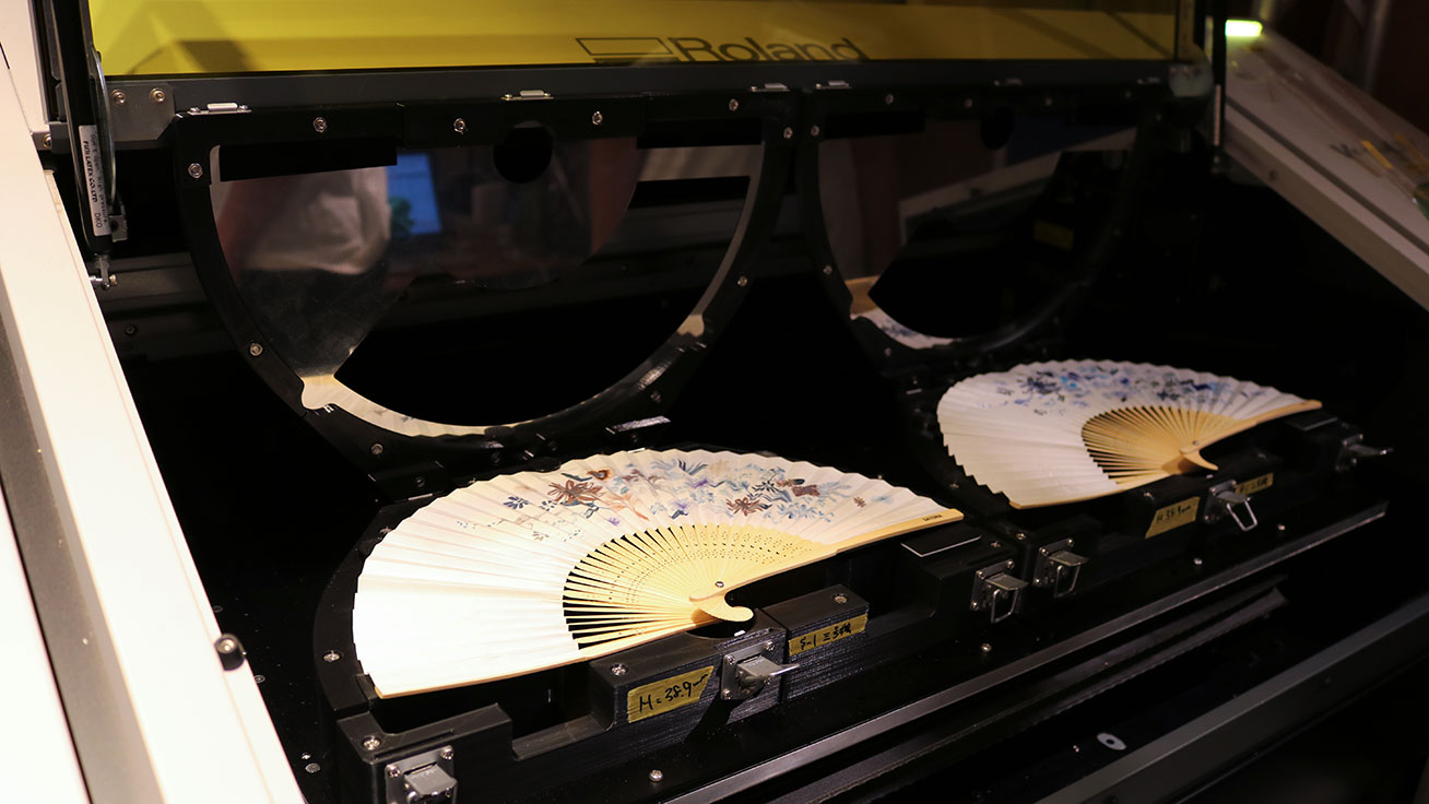 Personalized folding fans being printed at the gallery using UV printers
