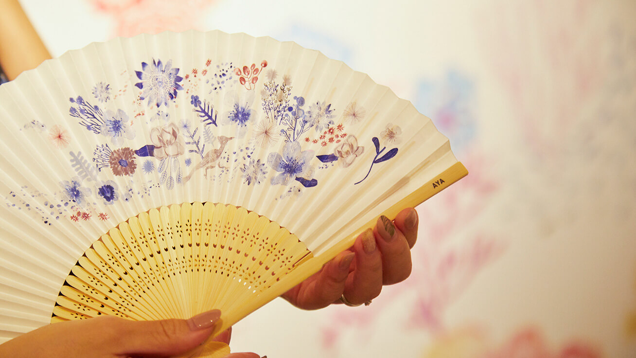 Custom-made folding fan designed to match color patterns in visitors' clothes