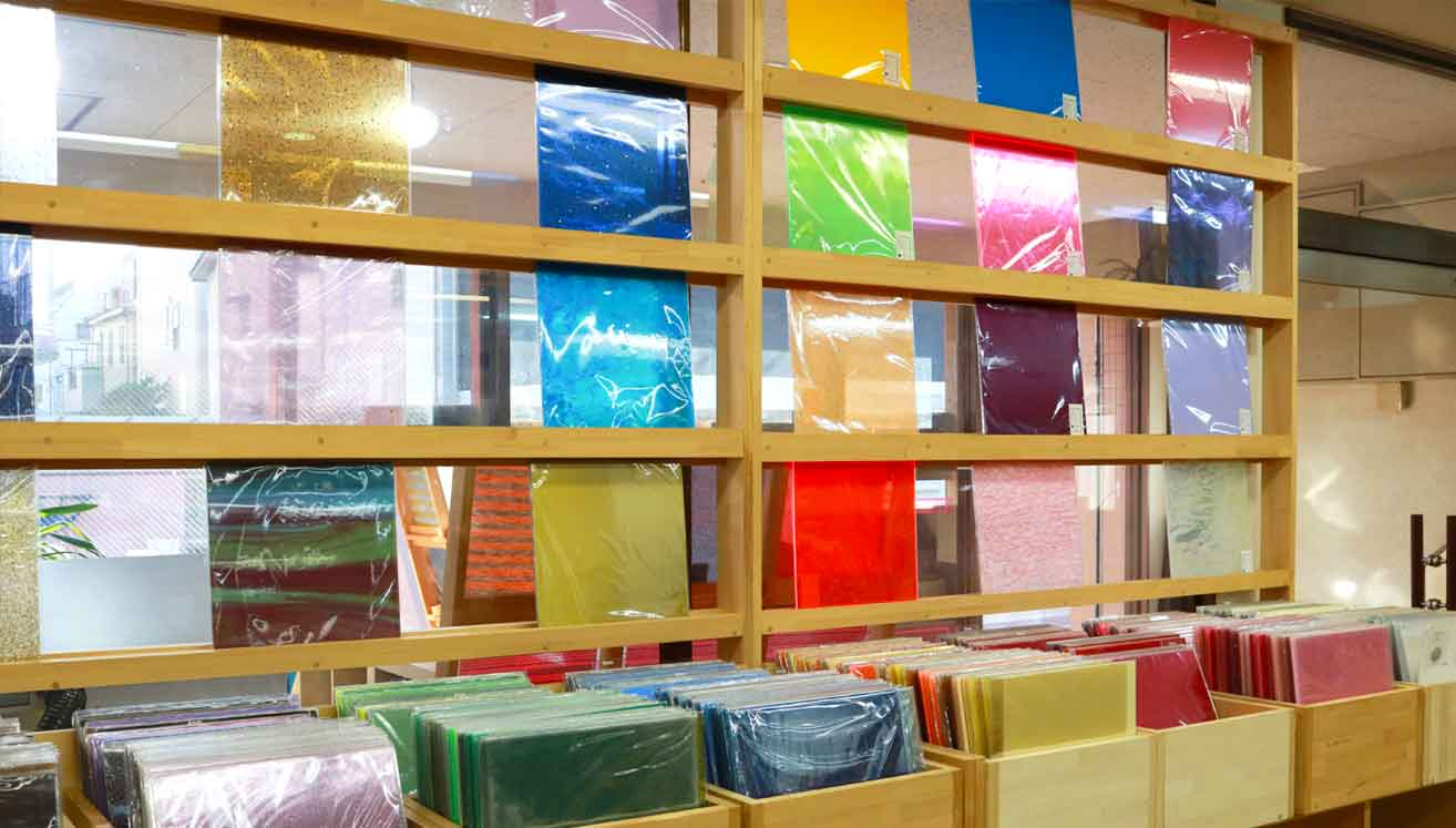 The showroom features acrylic sheets lined up like a record store.
