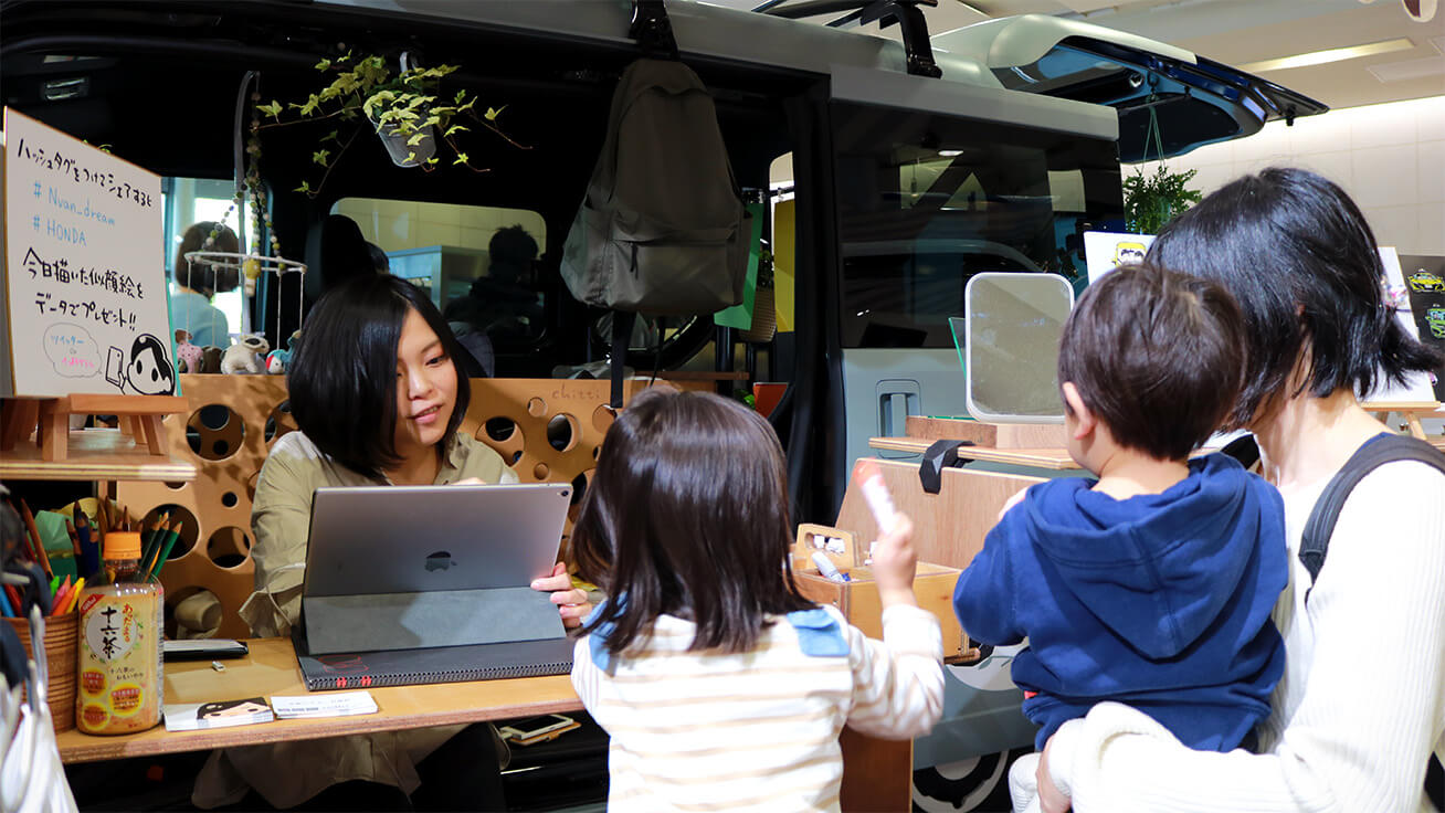 Illustrator Chihiro (left) chats with visitors while drawing their portraits.