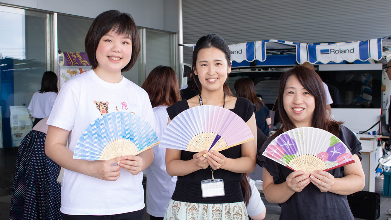 Employees proudly display their personalized folding fans with Meng.