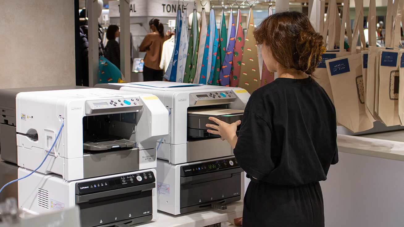 Printing out designs in the booth using the BT-12 direct-to-garment printer.