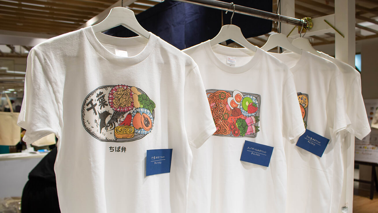 Exclusive event-only T-shirts with Chiba-themed lunchbox designs featuring local produce like peanuts (left).