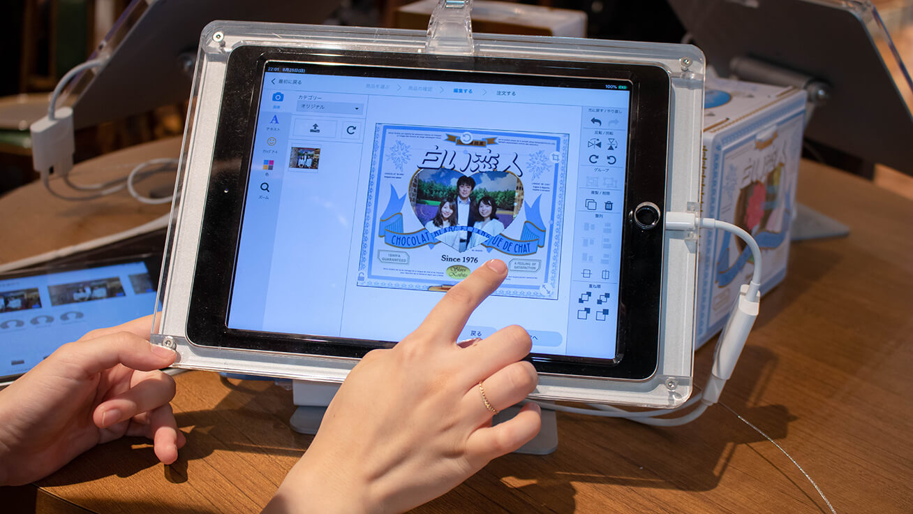Editing the layout on the tablet screen using cotodesign. Text and stamp artwork can also be added.