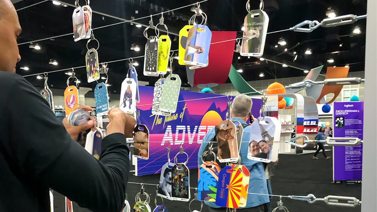 An Adobe MAX representative, adding new luggage tag designs to the mix of brilliant designs on display.