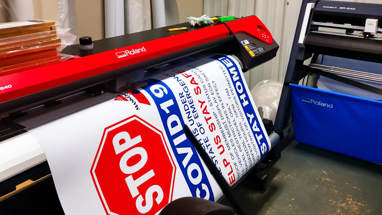 Large-format signs being printed on a Roland DG VersaEXPRESS RF-640 8-Color and cut with a CAMM-1 GR-640 cutter at Printology Digital for local Alberta businesses.