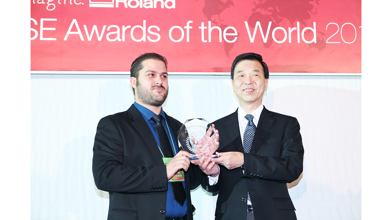 Mr. Yannig Van de Wouwer (left) receives the award from Masahiro Tomioka, President of Roland DG.